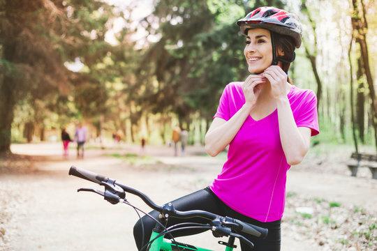 Bike helmet. Woman Putting Biking Helmet on Outside During Bicycle Ride.