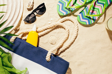 Beach accessories on the sand. Bag, colorful flip flops and hat and sunscreen. Summer vacation.