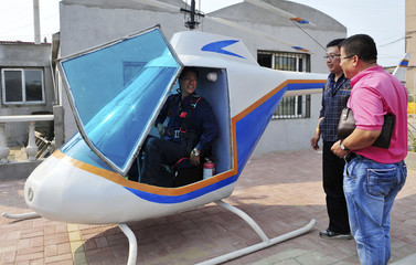 A researcher sits in a helicopter that has many of its components built by blacksmith Tian Shengying in Shenyang