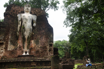 Travelers thai woman walking visit and travel take photo in ancient building and ruins of Kamphaeng Phet Historical Park