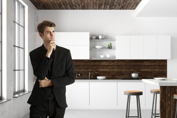 Handsome businessman in modern kitchen interior