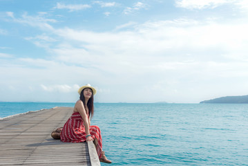 Summer Day. Smiling women relax and wearing red dress fashion sitting on the wooden bridge over the sea, blue sky background. Travel and Vacation. Freedom Concept