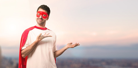 Superhero man with mask and red cape extending hands to the side and smiling for presenting and inviting to come on a sunset background
