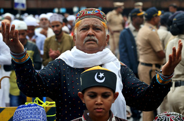 A man offers Eid al-Fitr prayers marking the end of the holy fasting month of Ramadan outside a railway station, in Mumbai