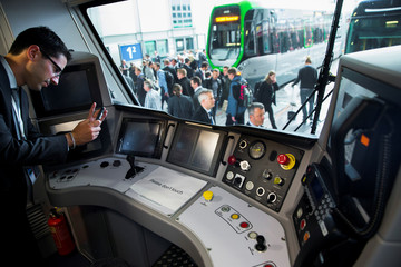 A man takes a picture of the cockpit of a Desiro City passenger train by Siemens Mobility at the InnoTrans railway technology trade fair in Berlin