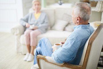 Senior man with cup of tea and his wife relaxing in living-room and having talk in the evening