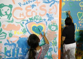 People paint on an art installation during Notte Bianca (White Night) celebrations in Valletta