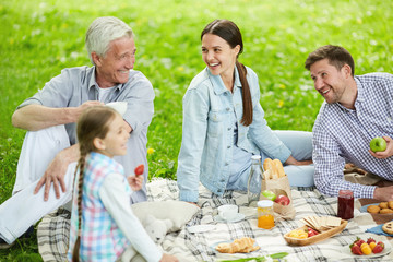Young couple and mature man laughing during summer picnic with little girl near by