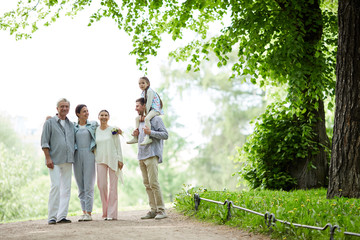Family of five spending summer day in park by walking under green foliage