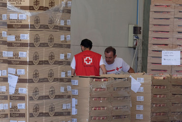 Red Cross volunteers store food at the logistical center a day before the arrival of refugee vessel Aquarius and two other Italian ships at the port of Valencia