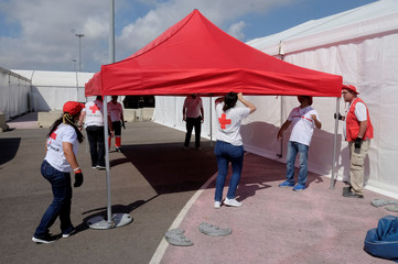 Red Cross volunteers mount a tent at the point of arrival of refugee vessel Aquarius and two other Italian ships expected tomorrow at the port of Valencia