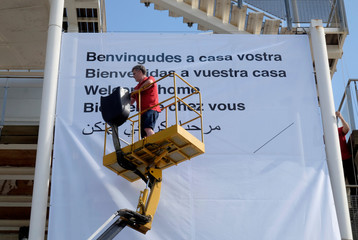 A Red Cross volunteer puts a banner at the logistical center a day before the arrival of refugee vessel Aquarius and two other Italian ships at the port of Valencia