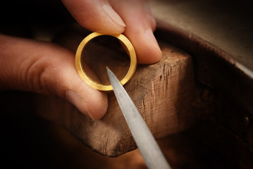 goldsmith hand holds a golden ring and works on it with a metal file, close up with copy space,  focus, narrow depth of field