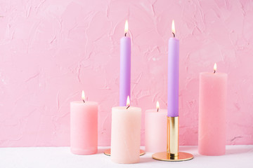Pink and violet  burning candles near by  pink  textured wall.