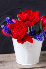 Red tulips and blue muscaries flowers in white bucket on aged textured  background.