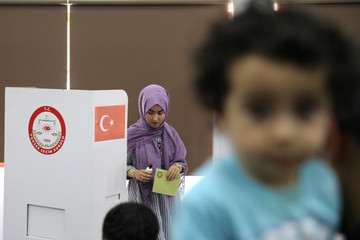 A voters casts her ballot for Turkey's presidential elections in the Turkish Cypriot northern part of the divided city of Nicosia