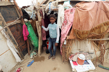 Boy stands outside his family's hut at a shantytown near the port of Hodeidah