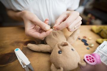 縫い包みを直す女性の手