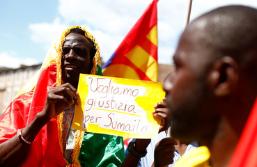 """A man with a banner reading """"We want justice for Soumaila"""" takes part in a national demonstration to show solidarity with migrants, after Soumaila Sacko a 29-year-old migrant agricultural worker, was shot and killed in southern Italy early this month, Rome"""