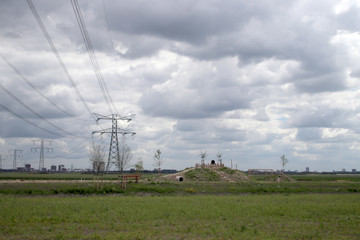 New nature playground in the polder in Zevenhuizen with powerlines and skyline of Rotterdam in background with dark clouds.