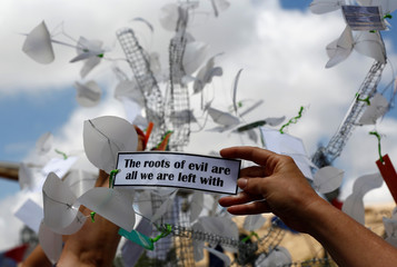 Activists from anti-corruption group Occupy Justice hang protest messages from a 'ghost tree of justice'  during a protest marking eight months since the assassination of investigative journalist Daphne Caruana Galizia, in Valletta
