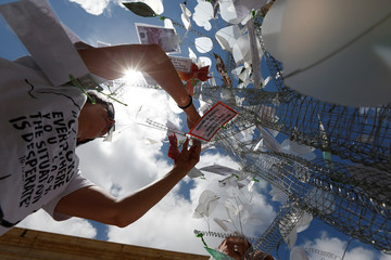 Activists from anti-corruption group Occupy Justice hang paper money and protest messages on a 'ghost tree of justice' during a protest marking eight months since the assassination of investigative journalist Daphne Caruana Galizia, in Valletta