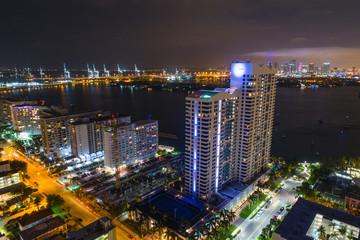 Aerial Miami Beach condominiums at night port in background