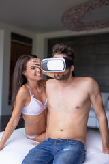 Young naked disappointed woman laughing on boyfriend in VR glasses