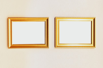 Blank golden picture frame on wall background