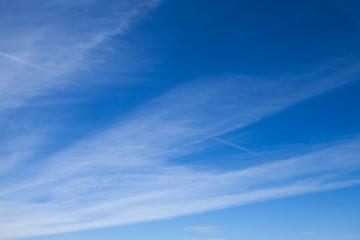 Blue sky with striped clouds. Contrail.