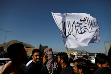 A member of the Taliban holds a flag in Kabul
