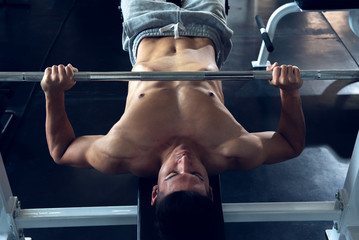 Asian sports young woman doing exercises with barbell on bench in the sport gym,  Bench Press machine equipment bodybuilder concept.