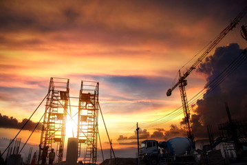 Construction site with crane and workers at sunset