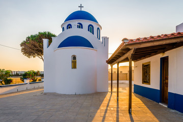 Church, Greece, Kos Island: warm sunset at a cozy little blue white church with red roof chapel in traditional colors which perched on the greeksy sea next to a small tree over the barren mountains