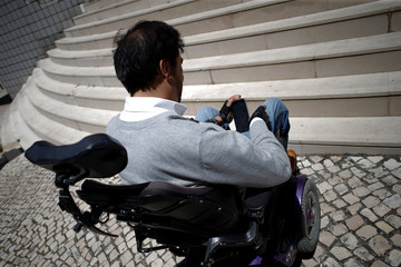 Wheelchair user Ricardo Teixeira uses the phone app he developed to report accessibility infringements to authorities, while unable to proceed to the sidewalk, in Lisbon