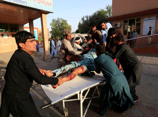 Men carry an injured man in a hospital after a car bomb, in Jalalabad city