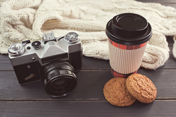 Hot coffee, oatmeal cookies, retro photo camera and scarf on a black table. Toning.