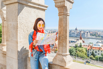 Pretty young asian traveler woman looking at map at Fisherman bastion fortress in Budapest, Hungary