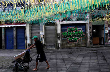 A man walks down the street decorated with the colours of the Brazilian flag to celebrate the World Cup at Saude neighbourhood in Rio de Janeiro
