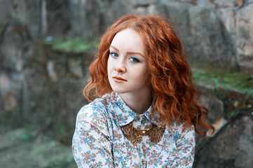 Portrait of a young red-haired curly girl with freckles in a vintage necklace