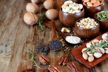 Different nuts and seeds in wooden spoons and bowls on a table