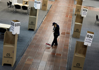 A worker cleans at polling station before the tomorrow's second round of the Colombian presidential election in Bogota