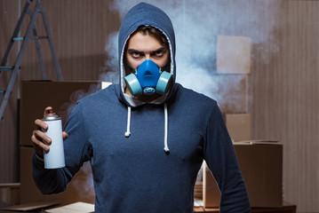 Graffiti painter in dark smokey room