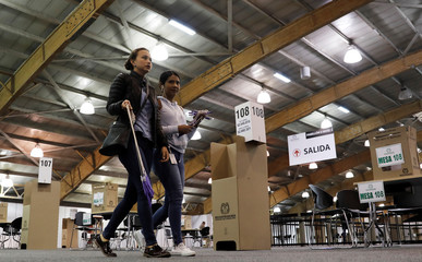 Workers carry pens at polling station before the tomorrow's second round of the Colombian presidential election in Bogota
