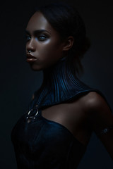 Portrait of black woman with gothic collar posing on dark background