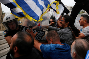 Protesters scuffle with riot police during a demonstration against the agreement reached by Greece and Macedonia to resolve a dispute over the former Yugoslav republic's name, in Athens