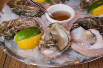 Fresh oysters with lemon and lime cheeks at a market in Normandy, France
