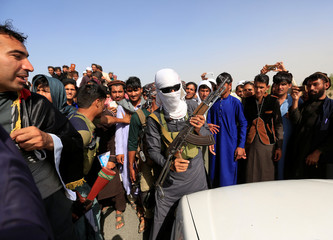 A Taliban (C) stands celebrates ceasefire with people in Rodat district of Nangarhar province, Afghanistan