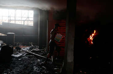 A man uses a bucket of water to help extinguish a fire in burned house where, according to local media, 6 people died, during a protest against Nicaragua's President Daniel Ortega's in Managua