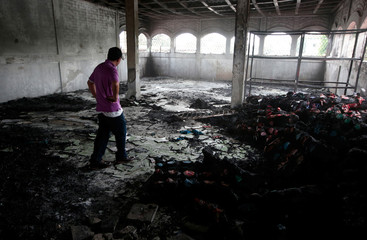 A man stands inside a burned house where, according to local media, six people died, during a protest against Nicaragua's President Daniel Ortega's in Managua
